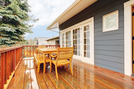 Wood deck during the rain with table and chairs and grey house. Stock Photo