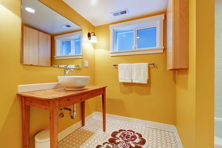 Orange bathroom with modern sink on the pine table with white tub. Stock Photo - 12760649