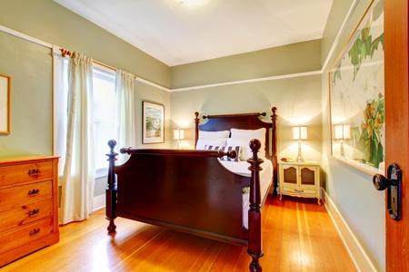 Green bedroom with cherry hardwood and dark bed.