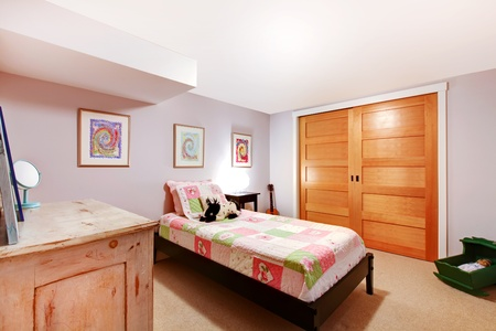 bedroom design: PInk girl kids bedroom in the basement with closet doors and dresser. Stock Photo