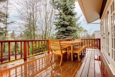 Wood deck during the rain with table and chairs and grey house. Stok Fotoğraf