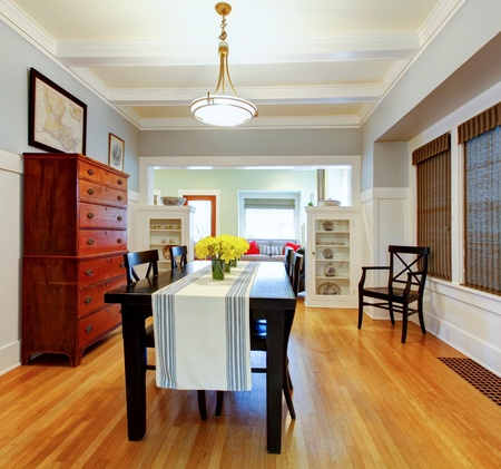 Dining room interior with large black table and wood dresser with grey blue walls.