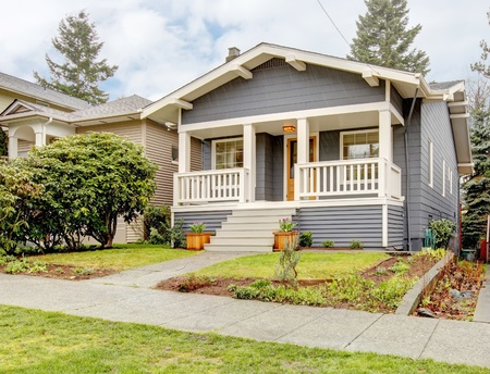 Blue grey smal craftsman style house with white porch. photo