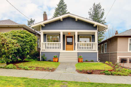 front of house: Small simple blue grey craftsman style house with white porch.