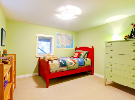 Cute child boy green bedroom with red bed.