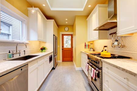 clean kitchen: Yellow and white bright kitchen with skylight and grey floor. Stock Photo