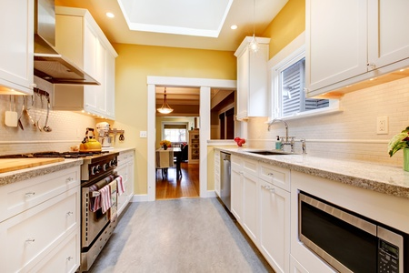 Narrow white and yellow kitchen with skylight and grey floor. photo