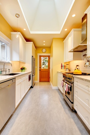 Yellow and white bright kitchen with skylight and grey floor. photo