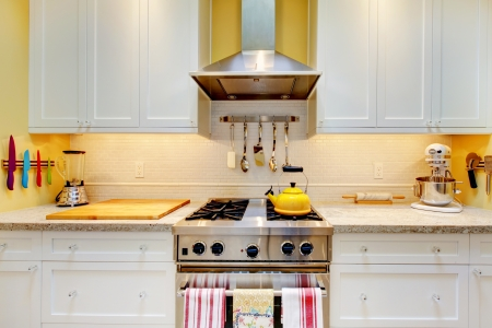 kitchen cabinets: Narrow white and yellow kitchen with cabinets close up. Stock Photo