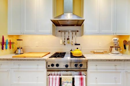 Smalle witte en gele keuken met kasten close up.