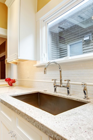 Large granite kitchen sink with window above it.
