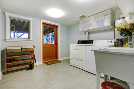 Large grey bright living room interior with washer and dryer.