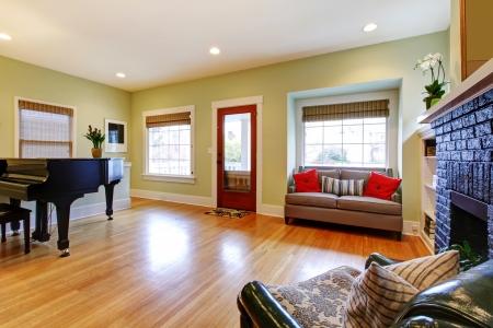 leuchtend gelbe wohnzimmer mit klavier und schwarzen kamin, Wohnzimmer