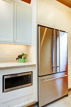 Stainless steal refridgirator with microwave and white cabinets. photo