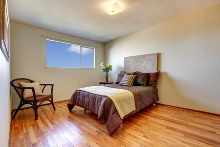 pulire camera da letto con pavimento in legno e letto marrone