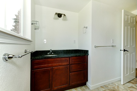 White new bathroom with mahogonay cabinet and no mirror. Stock Photo - 12760838