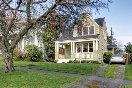 artesano: Pequeña casa verde exterior con porche y el coche de plata.
