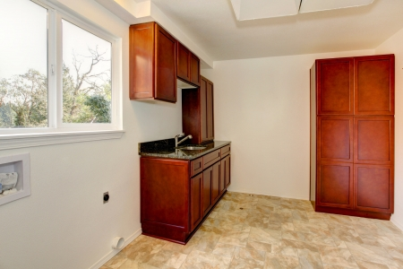 Empty laundry room interior with cherry wod cabinets.