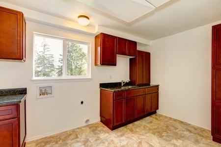 Bright white new laundry room with dark cherry cabinets. Stock Photo