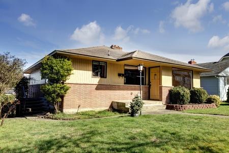 Yellow brick American rambler exterior with front wood door.