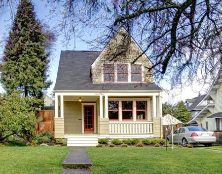 Green craftsman style house with the silver car. photo