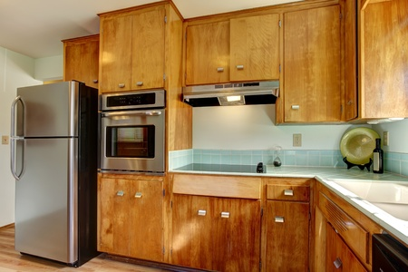 Wood kitchen with blue tiles and stainless steal appliances. photo