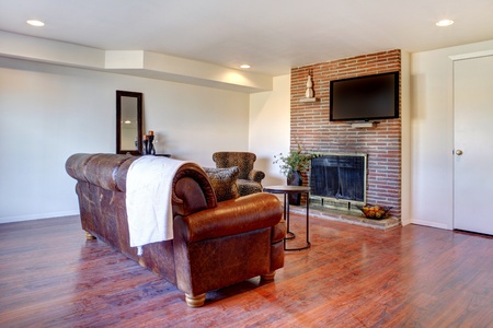 leren bank: Grote witte woonkamer met lederen sofa en open haard. Stockfoto