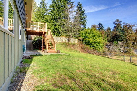 Backyard with large lot and grey hosue with deck on the hill. Stock Photo - 12924063