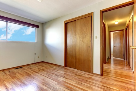 Empty bedroom with shiny hardwood floor and open door to hallway. photo