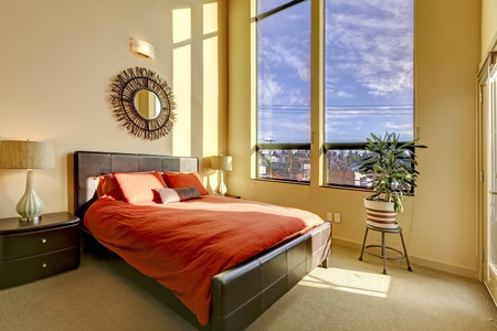 nightstand: Large high ceiling bedroom with red bed and yellow walls. Stock Photo