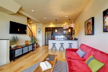 Yellow large living room with red sofa and brown kitchen. photo