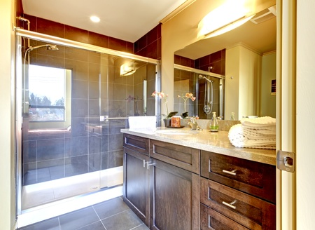 bathroom mirror: Modern new bathroom with wood cabinet and glass shower. Stock Photo