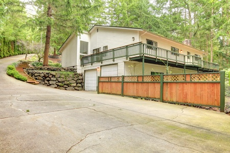 Beige American house in the woods on the hill with fence and porch. photo