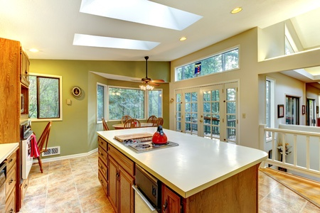 Large green country kitchen with skylights and wood cabinets.