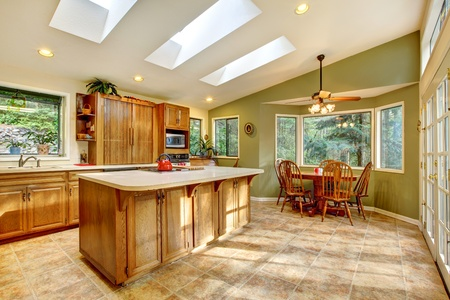 country kitchen: Large green country kitchen with skylights and wood cabinets. Stock Photo