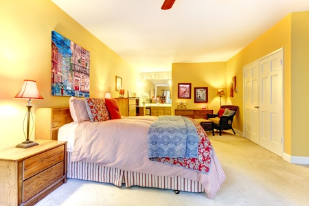 Large yellow bedroom interior with red bed and art. Stock Photo - 12913816