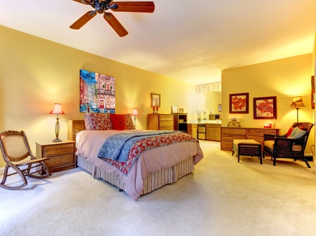 Large yellow bedroom interior with red bed.