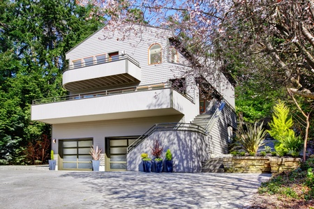 Light brown modern house exterior in spring forest with cherry blossom. Stock Photo - 13122574