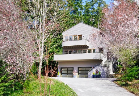 Light brown modern house exterior in spring forest with cherry blossom. Stock Photo - 13122565