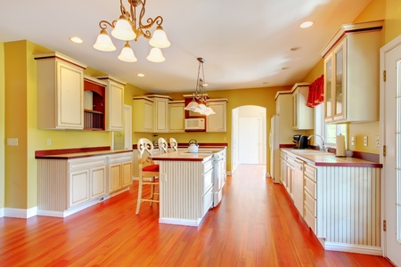 Gold kitchen with white antique cabinets and cherry hardwood. Stock Photo - 13122474
