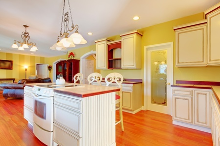 cherry hardwood: Gold kitchen with white antique cabinets and cherry hardwood.