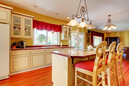 Gold kitchen with white antique cabinets and cherry hardwood. photo