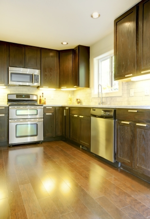 Modern luxury new dark brown and white kitchen with stainless steal appliances. photo