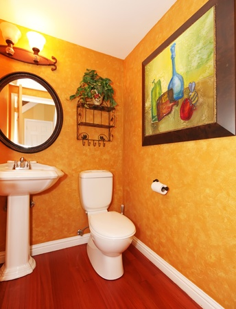 Orange small bathroom with large painting. photo