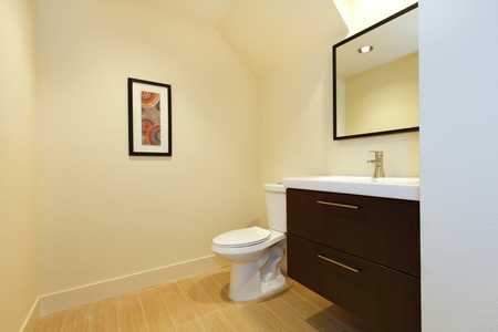 Simple new modern bathroom with brown cabinet and beige floor. Stock Photo