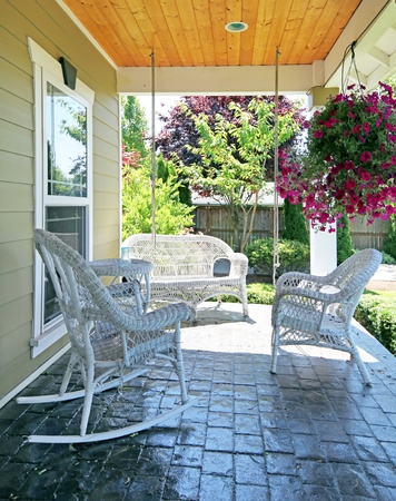 front porch: Front porch with white outdoor furniture and flowers. Stock Photo