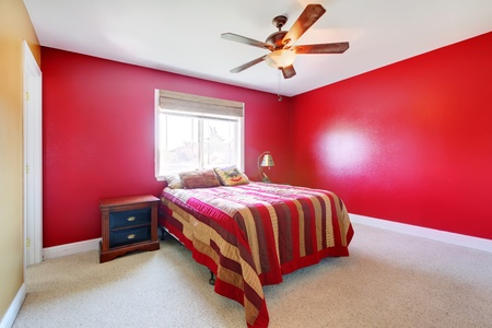 Simple red bedroom with bed and nightstand. photo