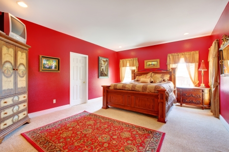 Large red bedroom with old bed and two windows.  photo