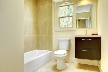 New modern yellow bathroom with beige tiles and brown cabinet.