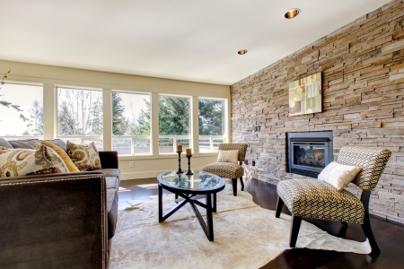 Beautiful modern large bright living room with dark floor and stone wall.